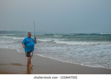 Hluhluwe , South Africa - Sep 24 2018:An elderly happy man caught a small fish on a manual fishing rod  in Sodwana bay which is a pristine beach near a lagoon and Isimangaliso wetlands during summer