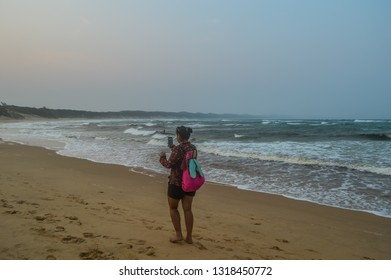 Hluhluwe , South Africa - Sep 24 2018:A young and beautiful Indian backpacker girl    talking on a video call in Sodwana bay  which is a pristine beach near a lagoon and Isimangaliso wetlands