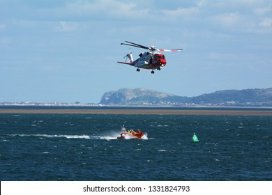 HM Coastguard helicopter on exercise with Beaumaris lifeboat on the Menai Strait off the coast of Anglesey