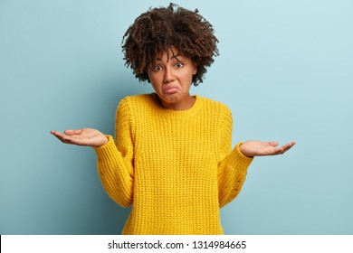 Hmm, I have no idea. Puzzled attractive curly Afro American woman spreads hands sideways, wears casual yellow loose jumper, purses lips, models over blue background, feels apathy and uncertainty