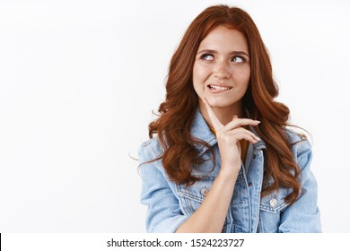 Hmm interesting idea. Attractive sassy redhead woman in denim jacket, look curious, biting lower lip from temptation, touch chin look aside as pondering, thinking what order, standing thoughtful