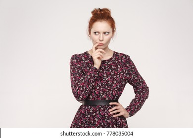 Hmm. Let me think. Isolaited studio shot on gray background of cute redhead woman with looking sideways and planning something.