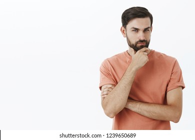 Hmm I am listening. Intrigued and interested handsome male 30s entrepreneur rubbing beard and squinting delighted, smirking as thinking, listening to good idea being excited and curious over grey wall