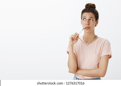Hmm might work. Portrait of unsure hesitant cute tanned female with messy bun biting frame of eyewear gazing at upper left corner thoughtful and confused as trying think, making choice over gray wall