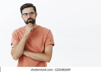 Hmm need think up plan. Portrait of determined and thoughtful creative perplexed guy smirking rubbing beard thoughtful looking right while making up idea trying solve troublesome situation