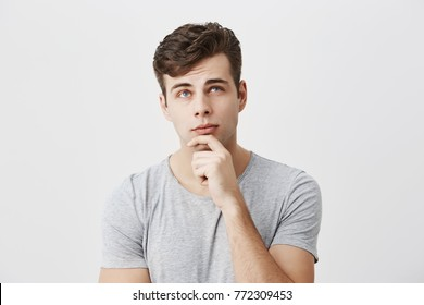 Hmm not bad. Concentrated thoughtful male student evaluating his chances to pass exam, keeps hand on chin, tries to decide what he deserves. People, lifestyle, face expressions.