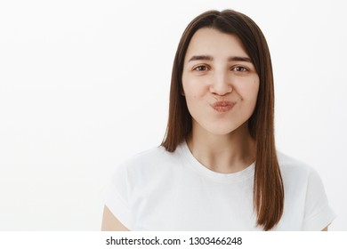 Hmm sounds tasty. Portrait of cheerful and excited pleased young girl folding lips and smiling as looking with desire at camera wanting try it standing amused and interested over gray background