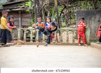H'mong Ethnic minority child playing the Spinning tops in Moc Chau Town, Son la province, Vietnam. Photo taken at: 01/ 02/ 2017.