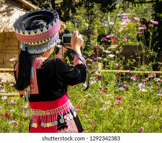 Hmong girl using a digital camera to taking pictures of flowers.