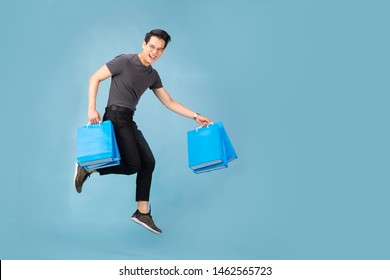 Hnadsome Asian man jumping isolated over blue wall background. holding shopping bags.