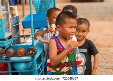 Hnong Main Ngam, Thailand - December 04, 2014: Children enjoy having an ice cream during a hot day in rural Thailand