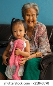 Hnong Main Ngam, Thailand - November 16, 2012: A very old great-grandma smiles while taking care for her great-grandchild