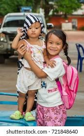 Hnong Main Ngam, Thailand - November 16, 2012: The elder girl taking care for her cousin after returning from school.
