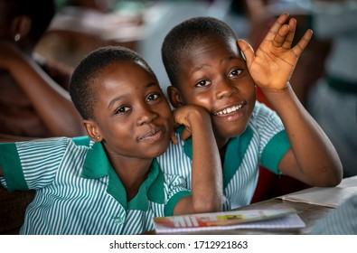 Ho, Asogli / Ghana - September 15, 2018: Two cute students in a rural school in Ghana, West Africa, wave and smile for a picture.