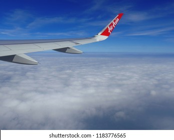 HO CHI MIN CITY, VIETNAM--MARCH 2018: An Air Asia aircraft takes to the skies with white fluffy clouds in view.
