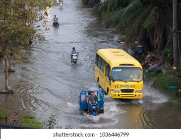Ho Chi Minh city (Saigon), Vietnam - 02/02/2018: School bus and motorbikes are moving in water on street. River water level raised due to heavy rains in Vietnam