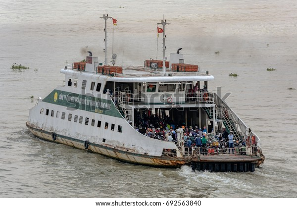 HO CHI MINH CITY (SAIGON), VIETNAM - April 26, 2017: Commuter ferry crossing the Saigon River with full load of walking and riding passengers.