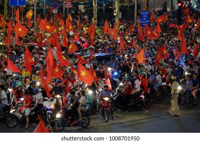 HO CHI MINH CITY, VIET NAM- JAN 23, 2018: Crowd of Vietnamese football supporter down the road to celebrate the win after soccer between U23 Vietnam and U23 Qatar, high view with red flag from fans
