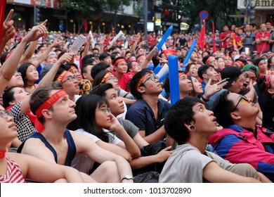 HO CHI MINH CITY, VIET NAM- JAN 27, 2018:  Portrait of Vietnamese football fans sit and watch AFC U23 soccer final match from outdoor Tv screen at Nguyen Hue walking street, amazing with red flag