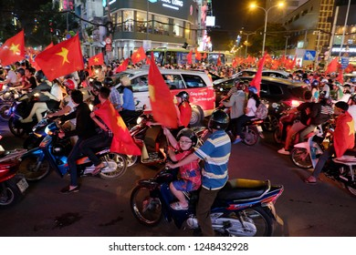HO CHI MINH CITY, VIET NAM- JAN 23, 2018: Young football fans down to road on motorbike with red Vietnamese flag to celebrate win over Qatar in AFC U23 Championship, soccer supporter with night storm