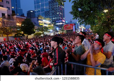 HO CHI MINH CITY, VIET NAM- JAN 27, 2018: Group of Vietnamese football fans sit and watching match on outdoor lcd screen to cheering for Vietnam team on walking street at night