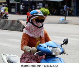 HO CHI MINH CITY, VIET NAM- APRIL 26, 2019: Vietnamese woman wear glasses, face mask, coat, gloves to sun protection, ride motorbike under high temperature in hot day, extreme weather, Vietnam
