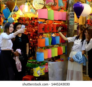 HO CHI MINH CITY, VIET NAM- SEPT 24, 2018: Group of Vietnamese beautiful young girls visit, have fun time, take a photo with friends at night lantern street, red vibrant at outdoor market