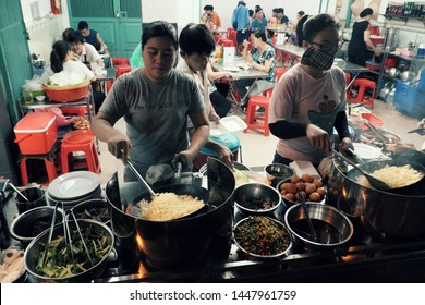 HO CHI MINH CITY, VIET NAM- JULY 05, 2019: Female chef making chicken rice for diners at restaurant at night food street, ingredient food as fried chicken, rice, vegetable, egg ready to serve