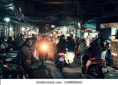 HO CHI MINH CITY, VIET NAM- JULY 05, 2019: bustling atmosphere on food street when people go out by motorbike  in dinner time for eating at outdoor restaurant night, Vietnam
