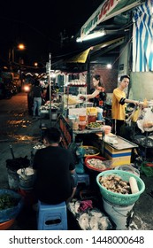 HO CHI MINH CITY, VIET NAM- JULY 05, 2019: Group of diners eating at outdoor restaurant night at food street, bustling atmosphere on street when people go out in dinner time, Vietnam