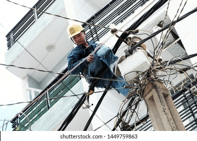 HO CHI MINH CITY, VIET NAM- JULY 12, 2019: Vietnamese electricity worker climb high on electric post to repair electricity network, man work in unsafe service at noon, Vietnam
