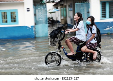 HO CHI MINH CITY, VIET NAM- SEPT 30, 2019: Two school girl ride electric bike crossing flooded street by high tide at evening, teen girl laugh when move in water, Vietnam