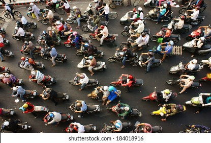 HO CHI MINH CITY, VIET NAM- MAR 27: Dense, crowed scene of city traffic in rush hour, crowd of people wear helmet, transport by motorcycle, stop at red light in stress situation, Vietnam, Mar 27, 2014