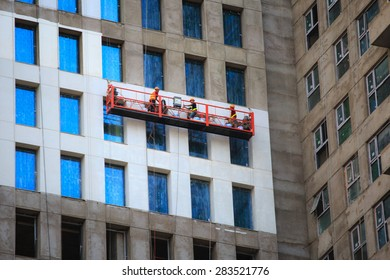Ho Chi Minh city, Viet Nam - April 10, 2015 Three workers are built on scaffolding with protective equipment safety