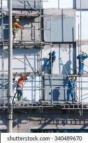 HO CHI MINH CITY, VIET NAM- NOV17: Group of Asian construction worker working on scraffold at apartment building site, Vietnamese man climbing, danger, unsafe for builder, Saigon, Vietnam, Nov17, 2015