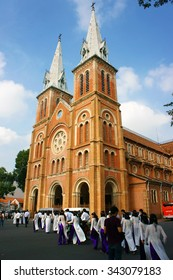 HO CHI MINH CITY, VIET NAM- NOV 24: Crowd of Vietnamese student in traditional dress, ao dai, shooting for yearbook at Saigon Notre Dame Cathedral, Vietnam, Nov 24, 2015