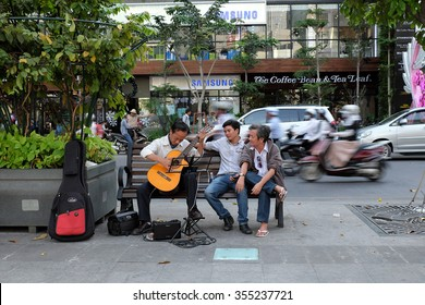HO CHI MINH CITY, VIET NAM, DEC 24: Lifestyle of citizen at evening, group of man sitting on bench, play guitar to relax, crowded scene and calm on Nguyen Hue walking street, Vietnam, Dec 24, 2015