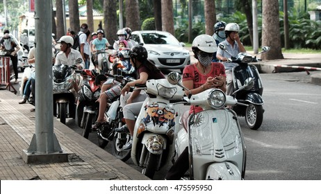 HO CHI MINH CITY, VIET NAM- AUG 28: Vietnamese people stop motorbike at roadway to play pokemon go, a hot game on smart phone, gamer staring at phone when sit on motorcycle near Tao Dan park, Vietnam