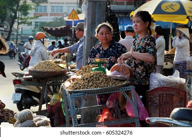 HO CHI MINH CITY, VIET NAM- MARCH 18, 2017: Vietnamese people sell peanut on pavement at Cho Lon open air market, street vendor work hard to earn money in city life at evening, Saigon, Vietnam