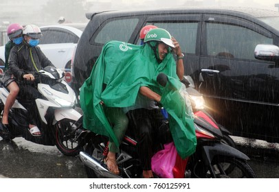 HO CHI MINH CITY, VIET NAM- NOV 21, 2017: Vietnamese people wear raincoat ride motorcycle, difficult move in heavy rain, high wind from bad weather by tropical low pressure after storm, Vietnam