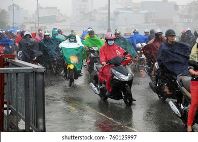 HO CHI MINH CITY, VIET NAM- NOV 21, 2017: Group of Asian people wear raincoat ride motorbike, difficult move in heavy rain, high wind from bad weather by tropical low pressure after storm, Vietnam