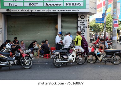 HO CHI MINH CITY, VIET NAM- NOV 21, 2017: Group of Asian people sit at outside restaurant at morning for breakfast, noodle soup is popular Vietnamese food, Vietnam