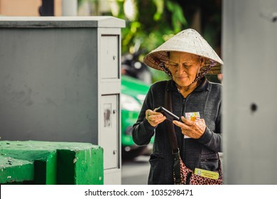 Ho Chi Minh City, Vietnam - January 05, 2016: old woman wearing a conical hat checking her smartphone on a street in Ho Chi Minh City, Vietnam.
