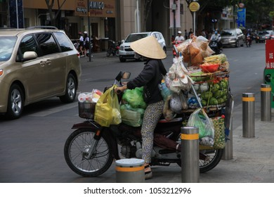 Ho Chi Minh City, Vietnam - February 22, 2018: Vietnamese Woman with Conical Hat   Vietnamese woman riding motorcycle in Ho Chi Minh City, Vietnam