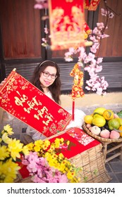 Ho Chi Minh city, Vietnam - February 03, 2018: Young girl wearing ao dai (Vietnamese traditional clothing) enjoy Vietnamese Tet holiday in Tet decoration objects