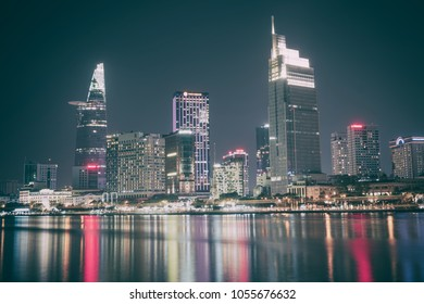 Ho Chi Minh city, Vietnam - March 11, 2018: Beautiful nightscene along the Saigon riverside with smooth water and reflection of skyscrapers included Bitexco financial tower