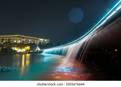 Ho Chi Minh city, Vietnam - March 24, 2018: Long exposure shot of Starlight Bridge (Anh Sao bridge) nearby the lake with blended color of red and green with water pouring and smooth reflection