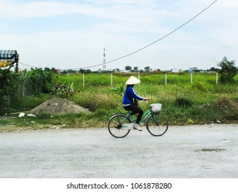 Ho Chi Minh City, Vietnam - December 15, 2013: local female vietnamese with traditional hat, riding a bike