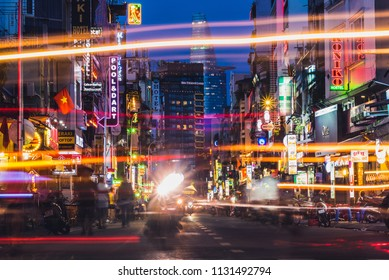 Ho Chi Minh City, Vietnam - May 2, 2018: vivid perspective of night Bui Vien Street. Lights, sign boards, Vietnam flag, Bitexco Tower, silhouettes, colorful lines of bikes' headlights (long exposure)