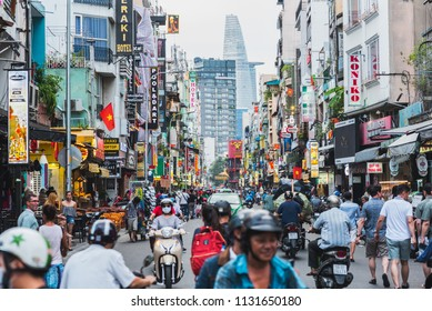Ho Chi Minh City, Vietnam - May 2, 2018: colorful perspective of Bui Vien Street with numerous hotel, bar and shop sign boards, crowded with people & motorbikes with a view of Bitexco Financial Tower